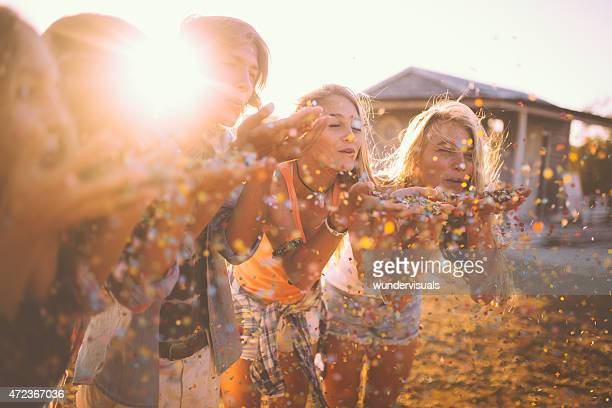 Teens blowing colourful confetti together outdoors with sun flare