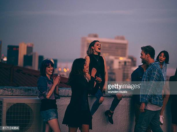 teens celebrating a funny rooftop party - roof stock photos and pictures