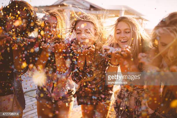 As adolescências Celebrando com colorido Confete fora na noite de Verão