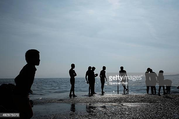 Teens from the Afghan city of Kunduz bathe while waiting with other recently arrived migrants to board a ferry to Athens on October 16 2015 in...