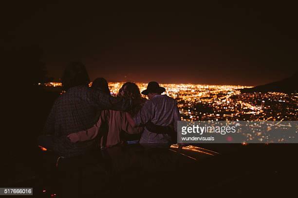 Teenager umarmen mit einem Cabrio Blick auf die Lichter der Stadt bei Nacht