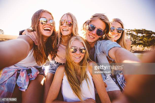 Teens in shades taking a group selfie outdoors