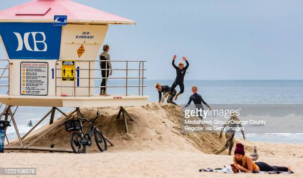 Teens jump off the sand mound at a lifeguard tower as beach goers enjoy the sun and sand near the Huntington Beach Pier in Huntington Beach on...