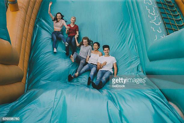 Teens Jumping Down Slide