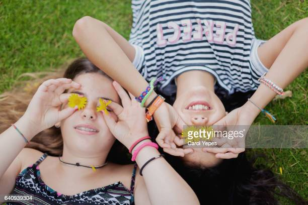 teens lying in grass with flowers in front of eyes