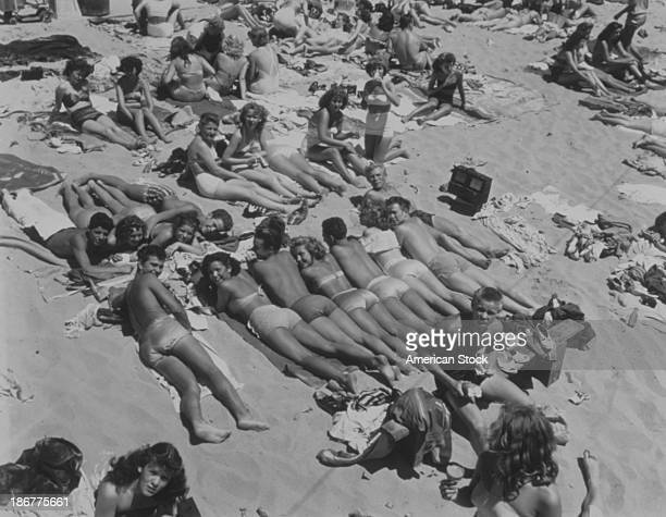 Teens lying on the beach in summer Hermosa Beach California 1970