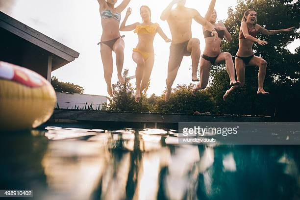 Teens mid-air while jumping into a still swimming pool
