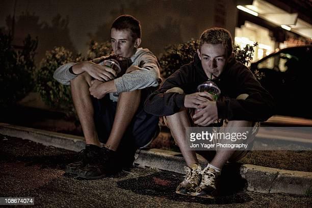 Teens on a curb with sodas