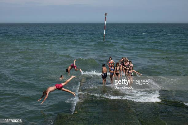 Teens play in the sea on the boat jetty at Viking Bay on June 26 2020 in Broadstairs Kent England The UK is experiencing a summer heatwave with...