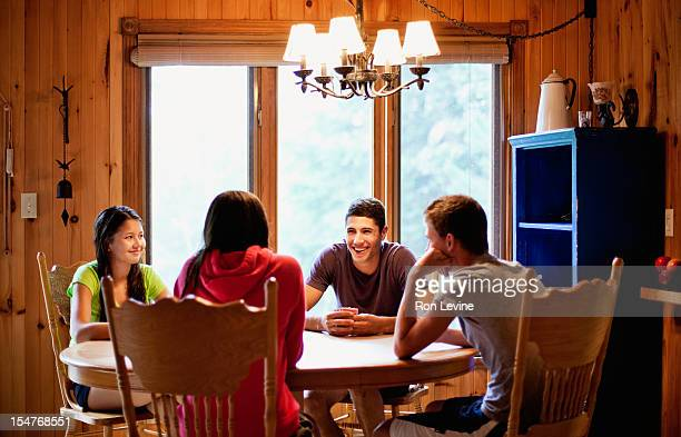 Teens playing a card game at a cottage
