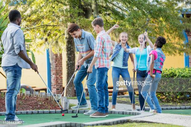 teens playing miniature golf, girls versus boys - miniature golf stock photos and pictures
