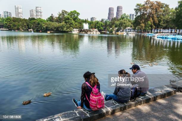 Teens sat by the lake at Bosque de Chapultepec forest park