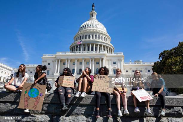 Teens sit along a wall at the US Capitol during the Global Climate Strike rally on September 20 2019 in Washington DC Thousands of people across the...