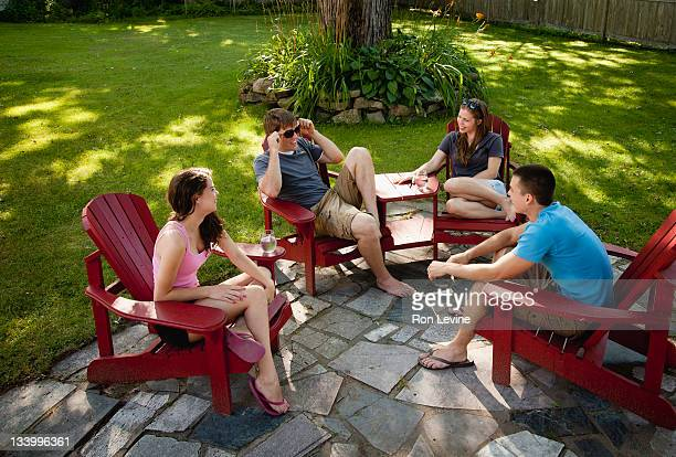 Teens sitting in a suburban backyard