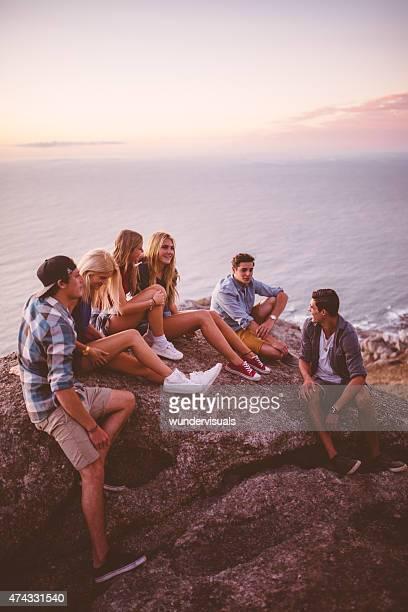 Teens sitting on rocks together at dusk