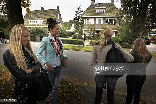 Teens stand in front of the house of a teenager who send a public Facebook party invite in Haren on September 21 2012 Police officers in Haren near...