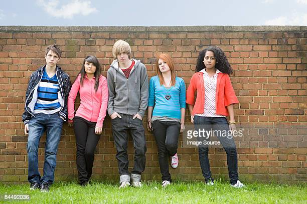 teens standing by wall - teenagers only stock pictures, royalty-free photos & images