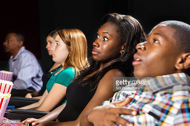 teens startled by horror film in movie theater - girl sitting on boys face stock photos and pictures