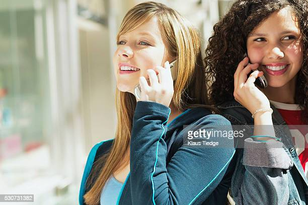 Teens talking on their cell phones at the mall