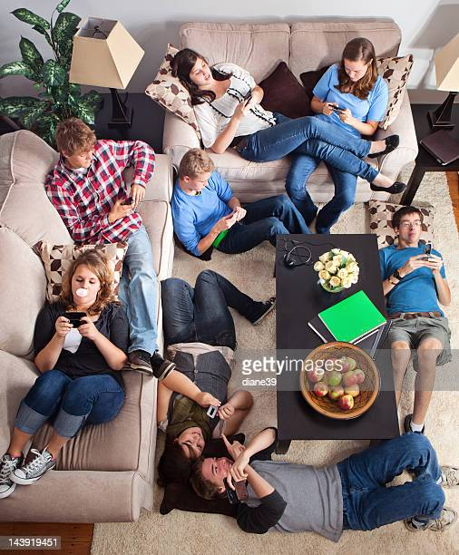 Teens texting in a living room