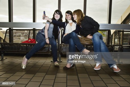 Teens traveling taking pictures with cell phone