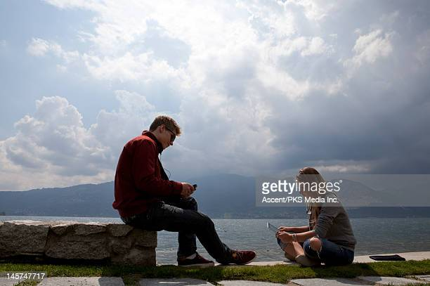 Teens use cell phone/ digital tablet by lake edge