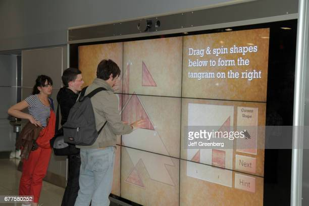 Teens using a digital interactive touch screen at John F Kennedy International Airport