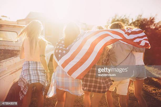 Teens walking with an American flag in sun flare