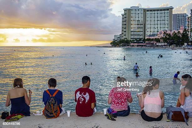 Teens watching the sunset at Kuhio Beach Park