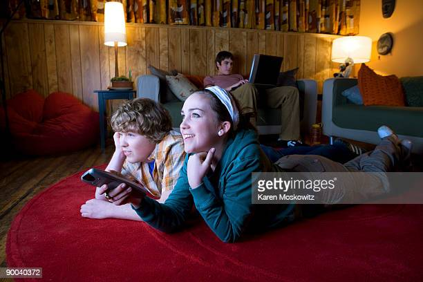 teens watching tv in rec room - part of a series stock pictures, royalty-free photos & images