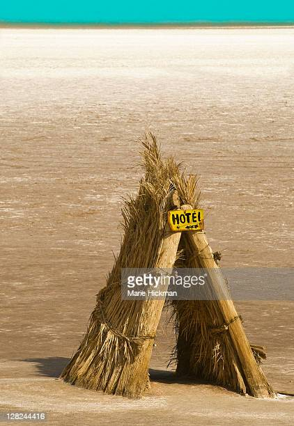 Tee-pee like structure made with leaves of palm trees with yellow three star hotel sign located on salt flats on the way to Tzour, Tunisia