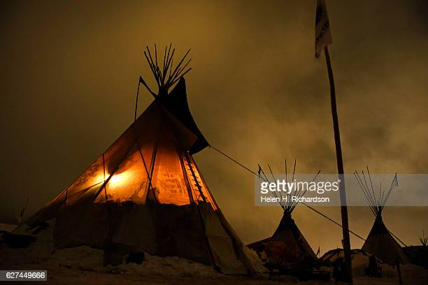 Teepees are nestled in the snow and lit by low lying clouds at Oceti Sakowin Camp on the edge of the Standing Rock Sioux Reservation on December 1,...