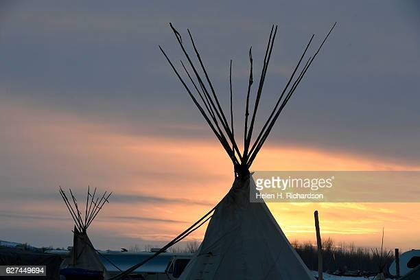 Teepees are nestled in the snow and lit by the setting sun at Oceti Sakowin Camp on the edge of the Standing Rock Sioux Reservation on December 1,...