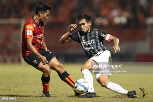 Teerasil Dangda of SCG Muangthong United dribbles the ball pass Shinnaphat Leeach of Chiangrai United during a Thai League 1 match between Chiangrai...