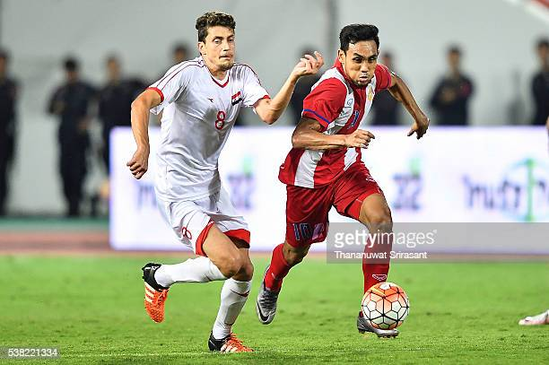 Teerasil Dangda of Thailand and Thaer Krouma of Syria competes for the ball during the 44th King's Cup match between Thailand and Syria at...