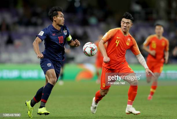 Teerasil Dangda of Thailand challenges with Shi Ke of China during the AFC Asian Cup round of 16 match between Thailand and China at Hazza Bin Zayed...