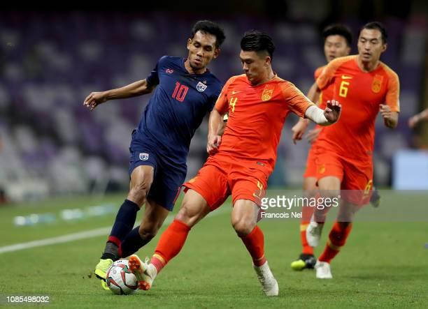 Teerasil Dangda of Thailand tackles with Shi Ke of China during the AFC Asian Cup round of 16 match between Thailand and China at Hazza Bin Zayed...