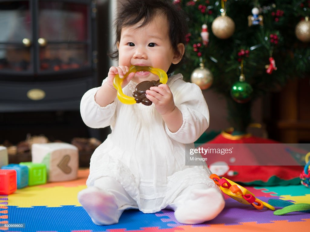 Teething baby girl playing with teething toy : Stock Photo