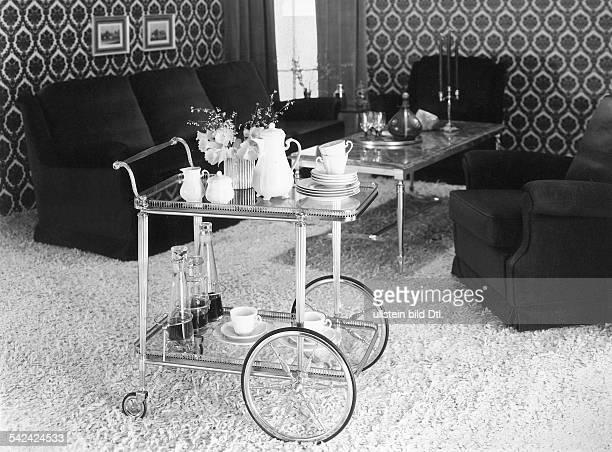 Teewagen vor einer Couchgarnitur im Hintergrund großgemusterte Tapete1973