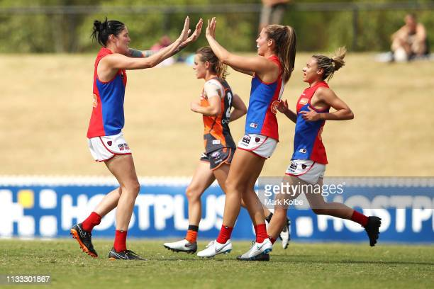 Tegan Cunningham of the Demons celebrates with her team mates after kicking a goal during the round five AFLW match between the Greater Western...