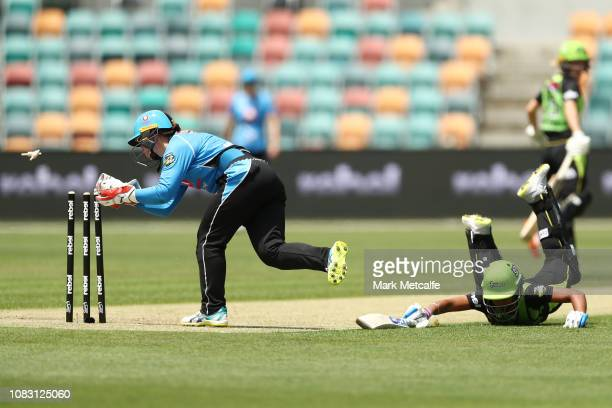 Tegan McPharlin of the Strikers attempts to run out Harmanpreet Kaur of the Thunder during the Women's Big Bash League match between the Sydney...