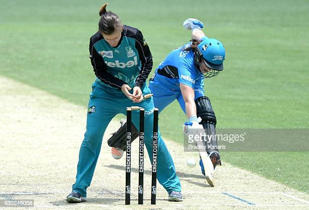 Tegan McPharlin of the Strikers is caught short of her ground by Jessica Jonassen of the Heat during the Women's Big Bash League match between the...
