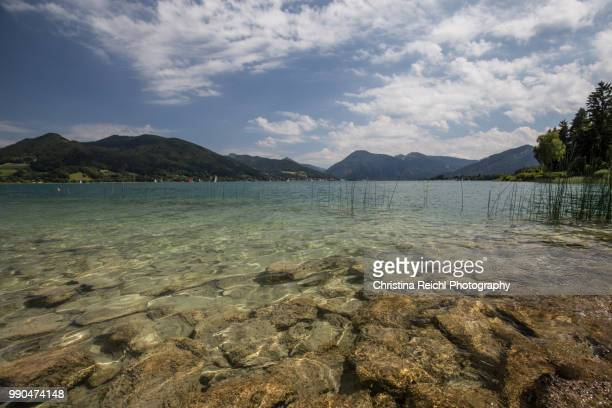 tegernsee on a sunny day with a few clouds - wasserrand stock-fotos und bilder