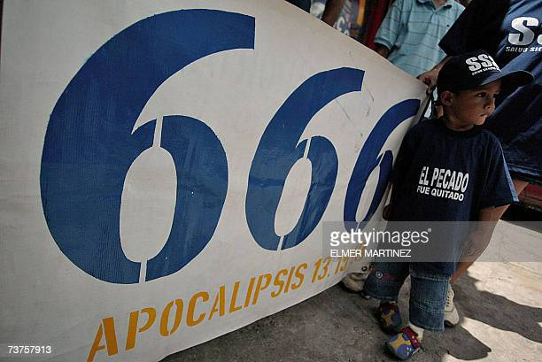 A kid stands next to a banner with the number 666 of the 'Growing in Grace' sect in Tegucigalpa 31 March 2007 According to the doctrine led by Puerto...