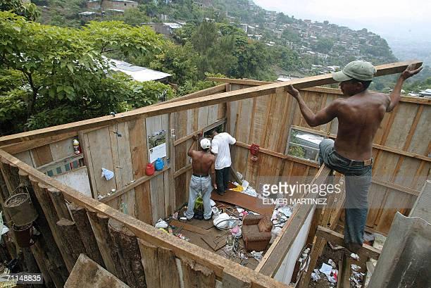 Tegucigalpa, HONDURAS: Habitantes de la colonia Villa Union trabajan desmontando su casa que fue afectada por un derrumbe en Tegucigalpa, el 7 de...