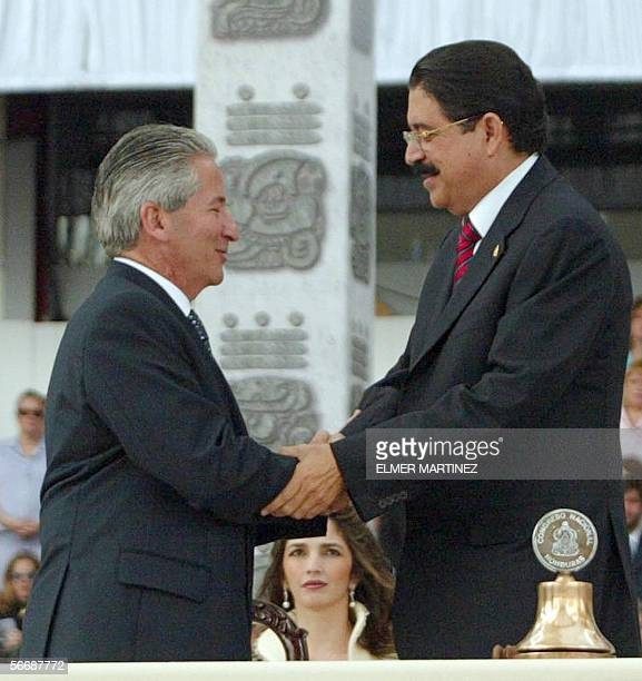 The new Honduran President Manuel Zelaya Rosales is congratulated by the outgoing President Ricardo Maduro after receiving the ceremonial sash in...