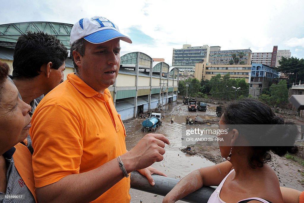 Tegucigalpa mayor Ricardo Alvarez (2-L) speaks to shopkeepers of the La Isla market, which was partially destroyed by tropical storm Agatha in Tegucigalpa, on June 1, 2010. Seventeen people were killed in Honduras as a result of Agatha, according to official figures. AFP PHOTO/Orlando SIERRA