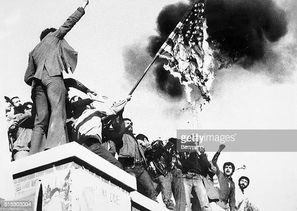 Teheran, Iran: Demonstrators perched atop of the United States Embassy wall, burn an American flag, the fourth American flag to be burned since the...