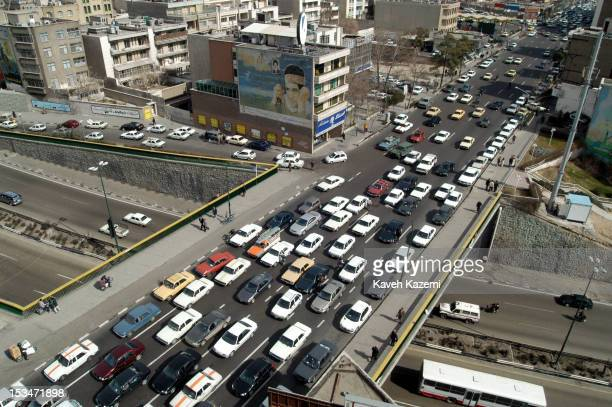 Tehran, Iran, 22nd February 2004: A busy Tehran street and underpass shadowed by a large mural of a young Basij volunteer, commemorating the war with...