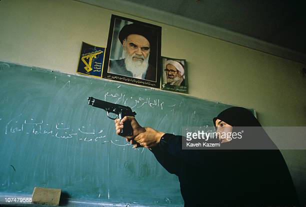 Basiji woman wearing black chador, familiarises herself with a Colt, in a school classroom in west Tehran, as part of mass mobilisation, in the final...